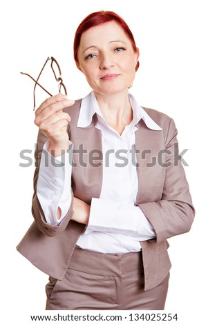 Nearsighted best ager business woman with red glasses in her hand - stock photo