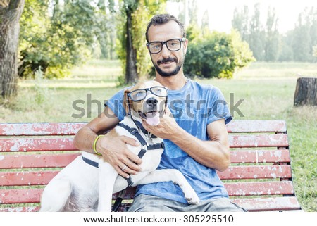 nearsighted man with his dog wearing glasses sitting on a bench