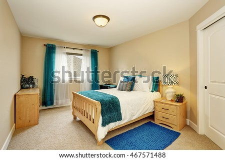 Neat Beige Bedroom With Turquoise Curtain And Wooden Bed. Northwest, USA