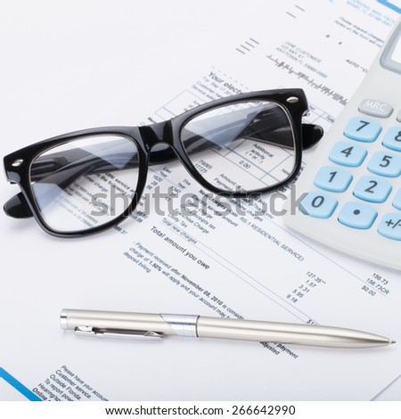 Neat calculator with pen, glasses and utility bill under it - close up shot