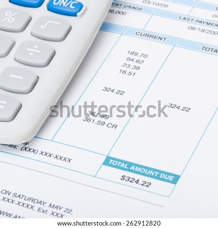 Neat calculator with utility bill under it - stock photo