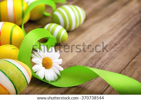Neat Easter decoration with happy bright spring colors of green, yellow and white on a wooden surface, with a daisy flower, curved ribbon and painted eggs - stock photo