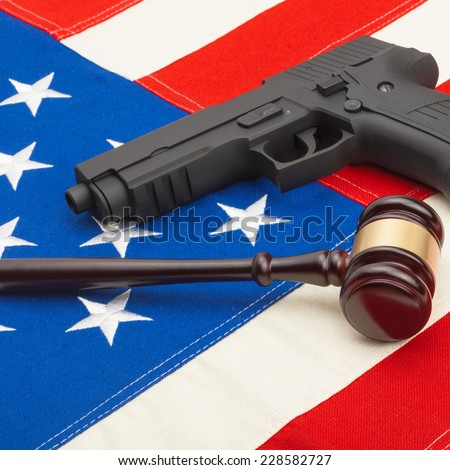 Neat judge gavel and gun over USA flag - studio shoot
