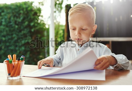 Neat methodical little boy doing art arranging sheets of white paper on an outdoor table on a patio with a serious expression alongside his colored crayons
