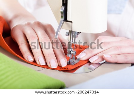 Neat tailor sewing orange fabric very precisely - stock photo