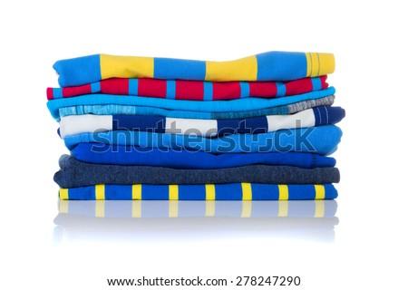 Neatly folded colourful summer shirts on a white background - stock photo