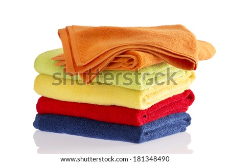 Neatly folded stack of soft fluffy towels in the colors of the rainbow on a reflective white background with the top orange towel turned at an angle to the others - stock photo