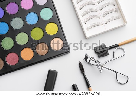 Necessary complexion of beauty products for every girl and woman to highlight the glory of eyes. Palette with various colors of eyeshadows, false lashes, curler and brushes create a flawless make-up. - stock photo