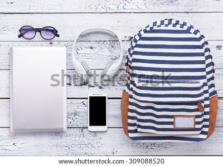 Necessary summer objects for vacation are represented on wooden background. Digital devices like laptop, smart phone and earphones are for communication with friends. - stock photo