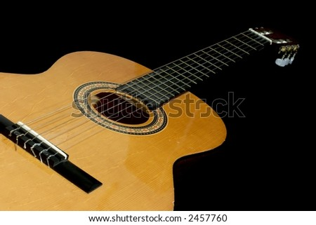 Neck and head of an acoustic guitar, isolated black background with copy-space - stock photo