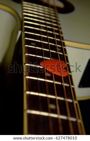neck guitar with heart pick on strings on black background