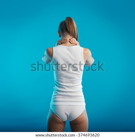 Neck spasm and ache. Young female suffering from back pain. Concept of spine illness and treatment.   - stock photo