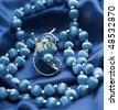 Necklace and brooch on the blue silk - stock photo