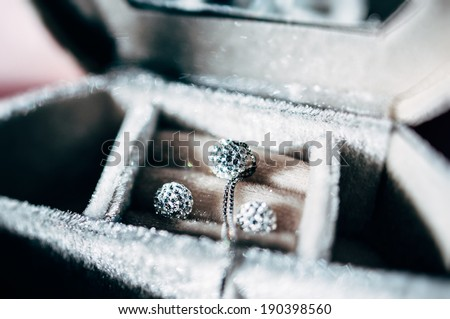 Necklace and pair of blue diamond crystal earrings in luxury storage box - beautiful jewelry - tilt-shift lens used to outline the object and to emphasize the attention on them - stock photo