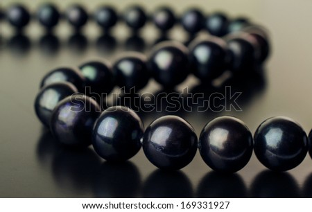 necklace of black pearls on a black background