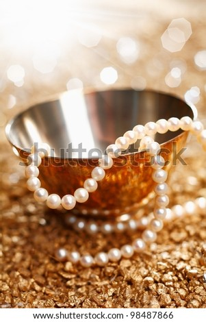 Necklace of matched pearls and a silver bowl with a festive sparkling bokeh of party lights