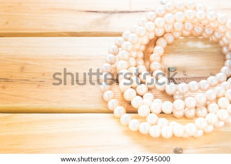 necklace of perls on the wooden board.