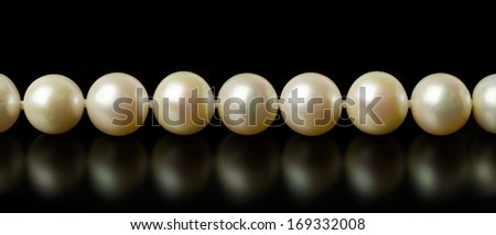 Necklace of white pearls isolated on black
