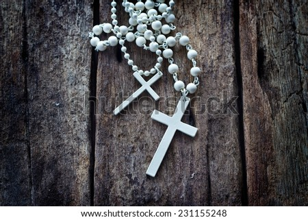 necklace white crucifix on old wooden table - stock photo
