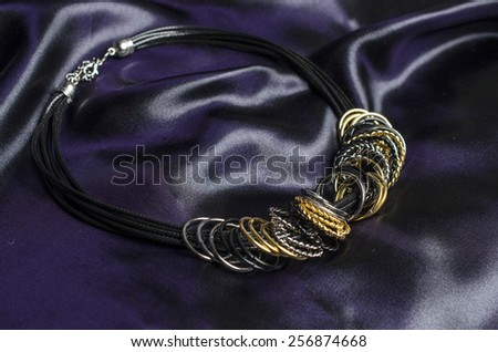 Necklace with rings on a silk background