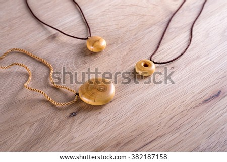 Necklaces made of wood on wooden background - stock photo