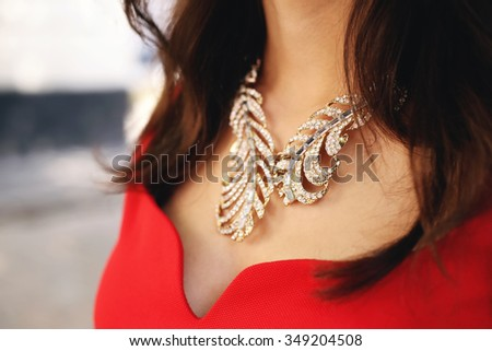 Neckline with a luxurious necklace. Golden necklace with rhinestones. Necklace and a red dress. Girl in a smart dress. Element style. Fashion look. - stock photo