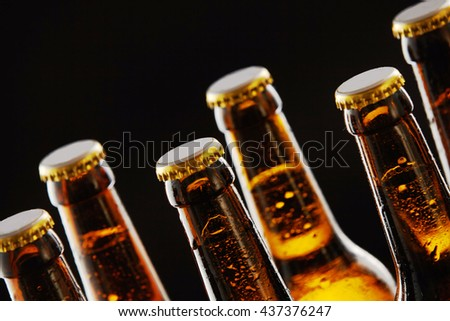 Necks of sealed beer bottles with condensation in a close up view over a black background in a tilted angle view conceptual of Oktoberfest