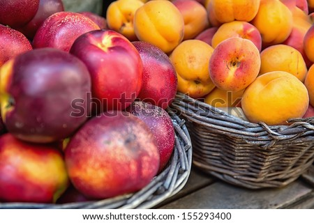 Nectarines and apricots in wicker baskets at the market - stock photo