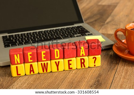 Need a Lawyer? written on a wooden cube in front of a laptop - stock photo