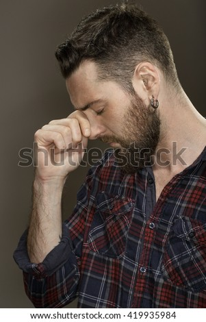 Need a rest. Portrait of a disappointed bearded man touching his face with his eyes closed at the studio on grey background. - stock photo