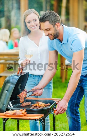 Need some help? Happy young couple barbecuing meat on the grill while other members of family sitting at the dining table in the background  - stock photo
