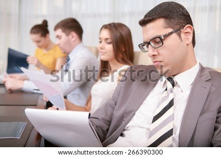 Need to check details. Confident strict business professional in formal wear and glasses reviewing business data at the meeting with his colleagues sitting in a row around the table - stock photo