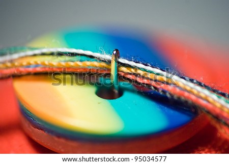 needle and colorful button close up - stock photo