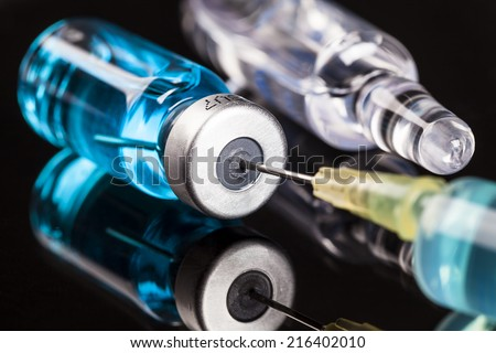 needle and injection in bottle on the glass - stock photo