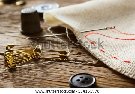 Needle and natural linen canvas texture for the background on wooden table  - stock photo