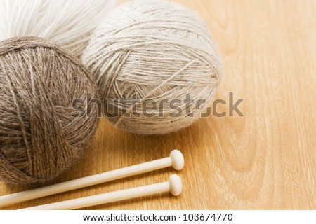 Needle and thread ball on wood table - stock photo