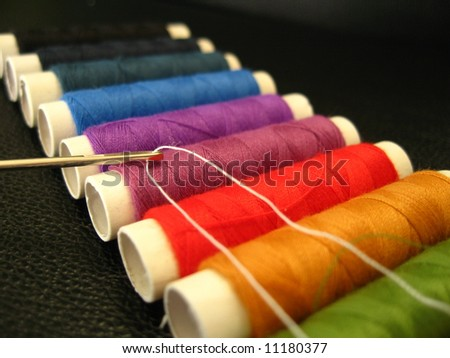 Needle with thread on coloured background - stock photo