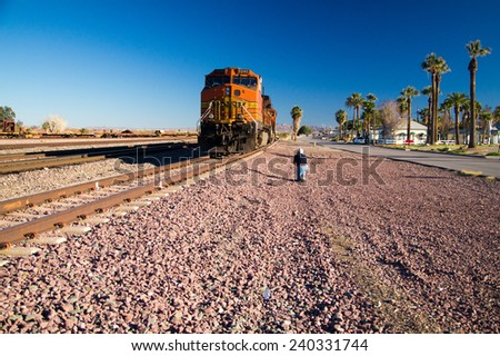 Needles, California/USA - February 5, 2013: Photographer captures image of distinctive orange and yellow Burlington Northern Santa Fe Locomotive freight train No. 5240 at town of Needles, California. - stock photo