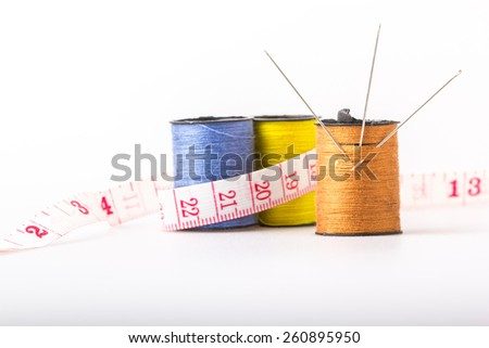 Needles in three of the lace into rolls sewing sewing thread winding brown with blue and yellow tape measure wrapped around the size of the background - stock photo