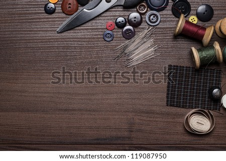 needles threads and buttons  on brown wooden table - stock photo