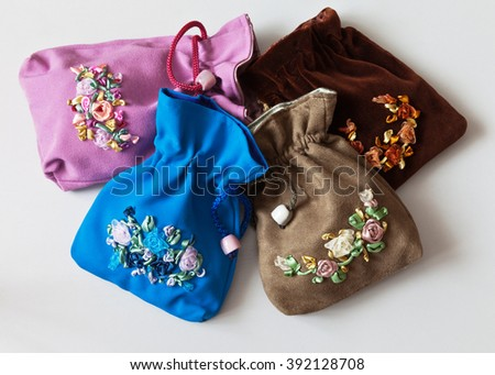 Needlework. Colorful gift bags for jewelry embroidered satin ribbons - stock photo