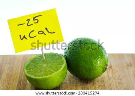 Negative-calories food, limes on a cutting board - stock photo