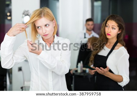 Negative client quarrels with barber in the barbershop client in the barbershop - stock photo