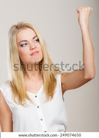 Negative emotions. Angry mad woman crazy furious woman shaking fist on gray. Threat. - stock photo