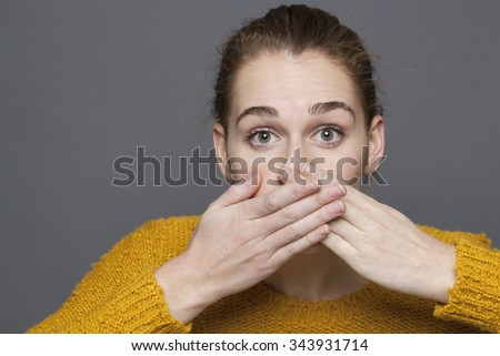 negative feelings concept - dumbstruck beautiful 20s girl covering her mouth for regret or mistake,studio shot on gray background - stock photo