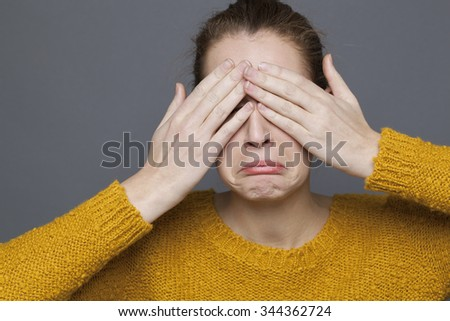 negative feelings concept - portrait of sad 20s girl covering her eyes,crying for problem of expression,studio shot on gray background - stock photo