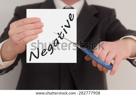 Negative, man in suit cutting text on paper with scissors - stock photo