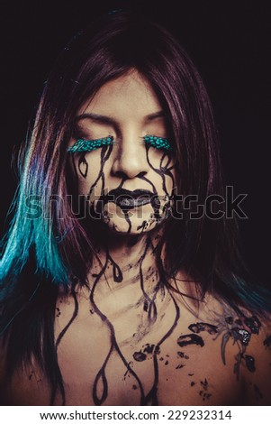 negativity concept, crying woman with tears and makeup dark light - stock photo