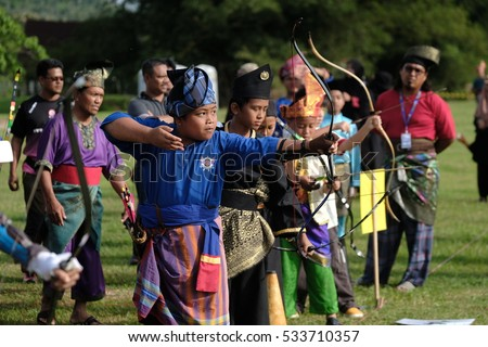 Negeri Sembilan, Malaysia - 11th December 2016 : A group of malay children dressed in malay traditional costumes shooting their arrows during an event Pertandingan Memanah Nusantara