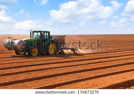 NEGEV, ISRAEL - FEBRUARY 11: John Deere tractor is working in the field on February 11, 2014 in Israel. John Deere is an american company and leading manufacturer of agriculture machinery.   - stock photo